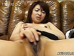Kinky dark haired Japanese lady tickles her wet pussy on the leather couch