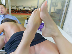 Boobalicious MILF is giving skilful footjob in the office